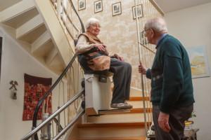 Älteres Paar hat einen Treppenlift in einer Wohnung –  So geht altersgerechtes Umbauen