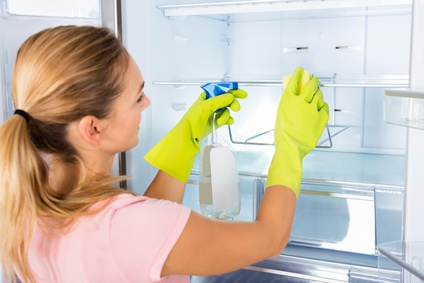 Junge Frau macht Frühjahrsputz im Kühlschrank