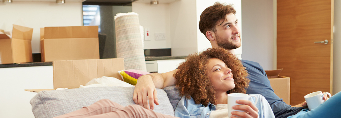 Couple Relaxing On Sofa With Hot Drink In New Home